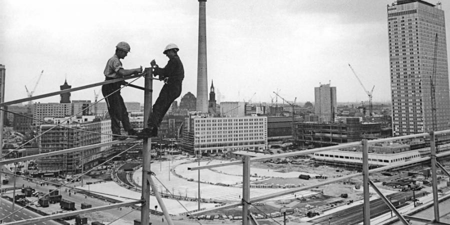 Photo of construction workers at a vertiginous height atop the Haus der Statistik, in the background the TV tower