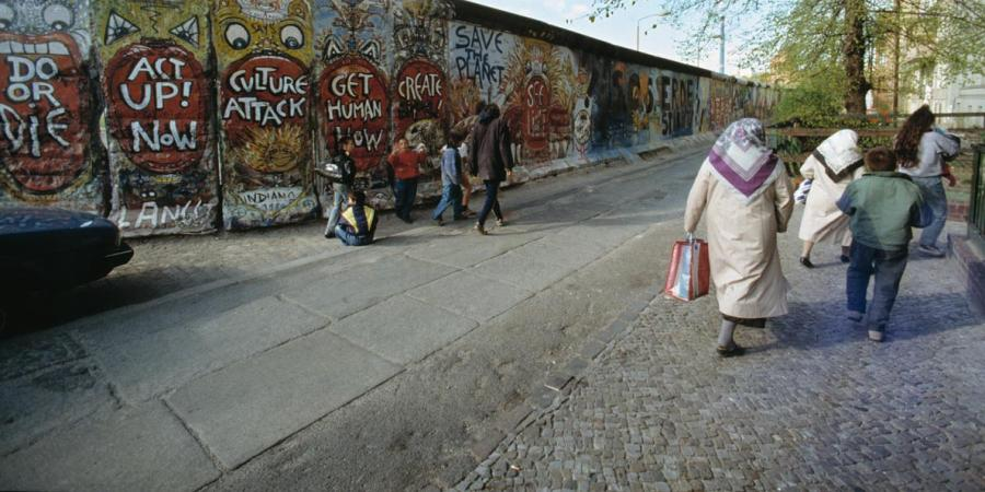 Photo of Turkish Berlin women and children in front of the Berlin Wall in Kreuzberg.