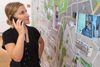 Photo of a woman watching a large format map of Berlin