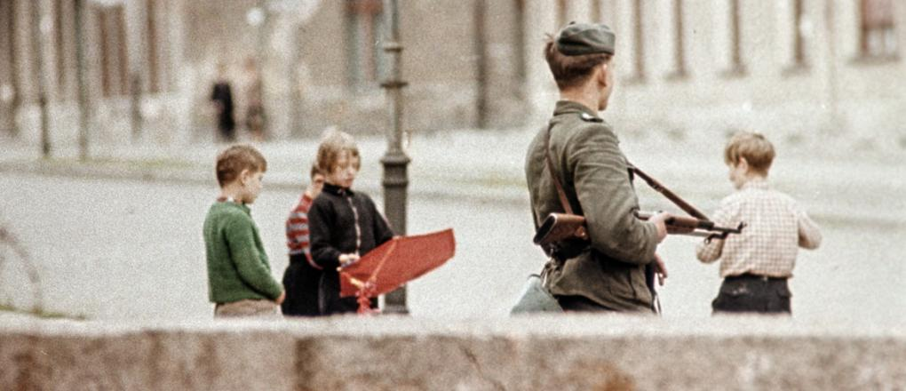 The Berlin Wall with armed guard and playing children, 1961