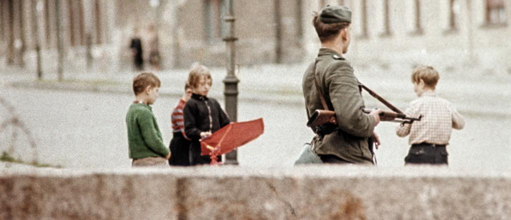 Armed guard and playing children at the Berlin Wall