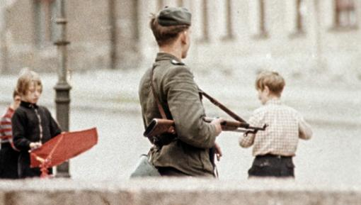 Photo of armed guard and playing children at the newly built Berlin Wall, 1961